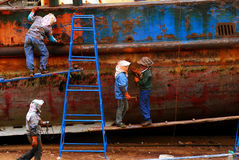 Woman repair old ship. In Xiapu,fujian province of China, there loacated a small old ship repair factory, this picture showed 4 woman remove the rust of the iron Royalty Free Stock Images