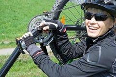 Woman repairing bicycle outdoors Royalty Free Stock Photos