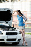 Woman repairing the broken car on the highway Royalty Free Stock Photos