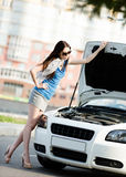 Woman repairing the broken car on the road Stock Image