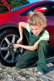 Woman repairing a car, unscrew the wheel Royalty Free Stock Image