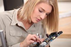 Woman repairing electronics Royalty Free Stock Photography
