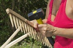 Woman repairing wooden garden rake Stock Photos