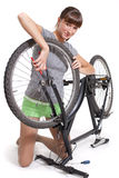 Woman repairs bicycle Royalty Free Stock Images