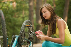 Woman repairs the bike Stock Photography
