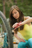 Woman repairs a bike Royalty Free Stock Photo