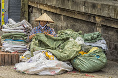 Woman repairs old plastic bags in the street of Hanoi. Royalty Free Stock Photography