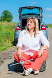 Woman after replacing the bursting of the wheel rests. Tired woman after replacing the bursting of the wheel rests Royalty Free Stock Images