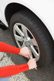 Woman replacing tire Stock Images