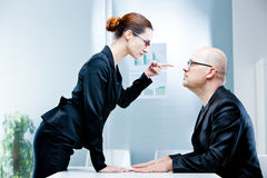 Woman reproaching man at work stock photos