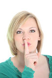 Woman requesting quiet with hushing gesture Royalty Free Stock Image