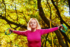 Woman Resistance training in park. Portrait of beautiful smiling sportswoman doing resistance training in park Stock Photo
