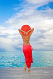 Woman resort red sarong. Woman in tropical elegant red sarong and wide brim hat on resort pier feeling carefree and happy on remote tropic island Royalty Free Stock Image