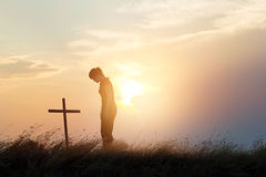 Woman respecting at the cross on the field of sunset background Stock Photography