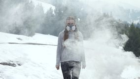 Woman in respirator in nature in smoke. Gas pollution stock video footage