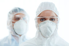 Woman in respirator. Young female in coveralls, eyeglasses and respirator looking at camera with her colleague on background Stock Photography