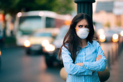 Woman With Respiratory Mask Out in Polluted City. Worried girl fighting urban pollution with safety measures Stock Photo
