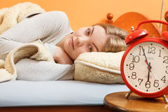 Woman rest in bed under blanket with alarm clock. Stock Images