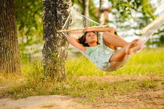 Woman rest in hammock. Young woman in green dress rest in hammock Royalty Free Stock Photo