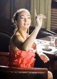 Woman at restaurant. Woman sits at the table and does a sign to the waiter at restaurant Royalty Free Stock Photos