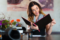 Woman in restaurant choosing food in menu. Young woman in a cafe or restaurant, looking in the menu card and choose Royalty Free Stock Photography