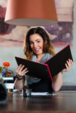 Woman in restaurant choosing food in menu Stock Photo