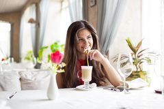 A woman in a restaurant is drinking cocktail Stock Photo