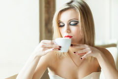 A woman in the restaurant is drinking coffee Stock Photos