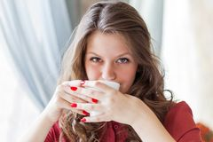 A woman in a restaurant is drinking coffee Stock Images