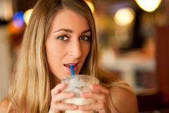 Woman in restaurant drinking milkshake Stock Image