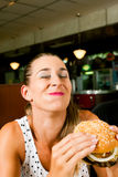 Woman in a restaurant eating hamburger Royalty Free Stock Images