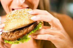 Woman in a restaurant eating hamburger Stock Photos