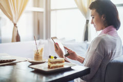 Woman in a restaurant holding digital tablet, browsing internet or connecting to wireless side view stock photography