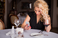 Woman at restaurant looking at her phone Stock Photo
