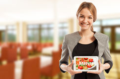 Woman restaurant manager holding tablet with menu. Woman modern restaurant manager holding tablet with menu on dining room background Royalty Free Stock Images