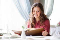 A woman in a restaurant with the menu in hands Royalty Free Stock Photo