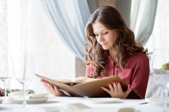 A woman in a restaurant with the menu in hands Royalty Free Stock Image