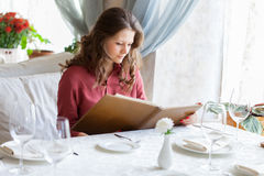 A woman in a restaurant with the menu in hands Stock Photos
