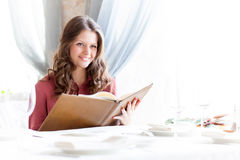 A woman in a restaurant with the menu in hands Royalty Free Stock Images