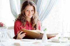 A woman in a restaurant with the menu in hands Stock Image
