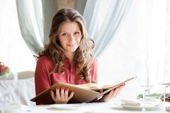 A woman in a restaurant with the menu in hands Stock Images