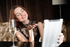 Woman in a restaurant relaxing with glass of champagne and tablet pc. stock image