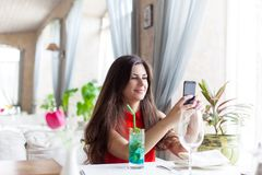 A woman in restaurant is taking photos Royalty Free Stock Photography