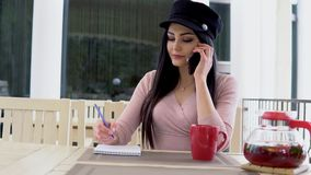 A woman in a restaurant talking on the phone and drinking tea. A woman in a restaurant talking on the phone and writes entries in a notebook stock footage