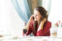 A woman in restaurant is talking to mobile phone Royalty Free Stock Image