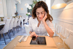 Woman in restaurant using tablet with blank screen Stock Photo