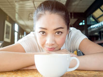 Woman rested in coffee cafe table. Asian woman rested on table in the coffee cafe with white cup of coffee Stock Photography