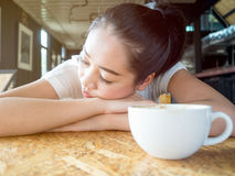 Woman rested in coffee cafe table. Asian woman rested on table in the coffee cafe with white cup of coffee Stock Images