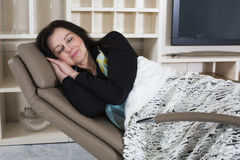 Woman resting in armchair Stock Images