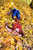 Woman resting on autumn leaves in park. Royalty Free Stock Images